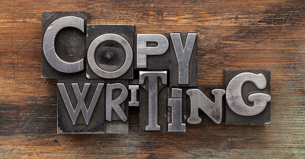 Metal typesetting blocks spelling out the word copywriting on a wooden table