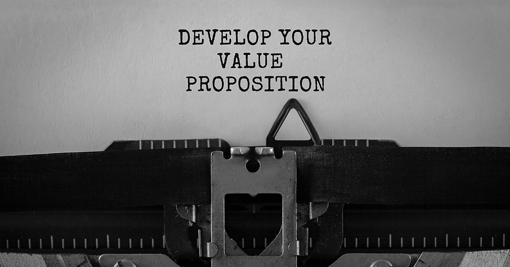 """""""Develop Your Value Proposition"""" typed on a piece of paper with an old typewriter in the forefront."""