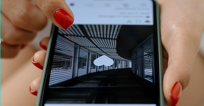An image of a woman's hand holding an iPhone that's open to the Instagram screen with a liked black and white photograph of a winding hallway.