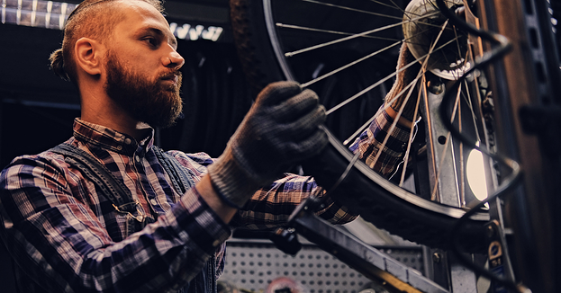 A young man repairing a bicycle tire in a cycling shop