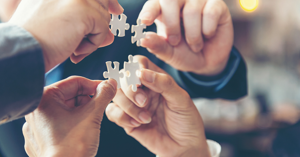 Four hands holding puzzle pieces together as a solutions concept.