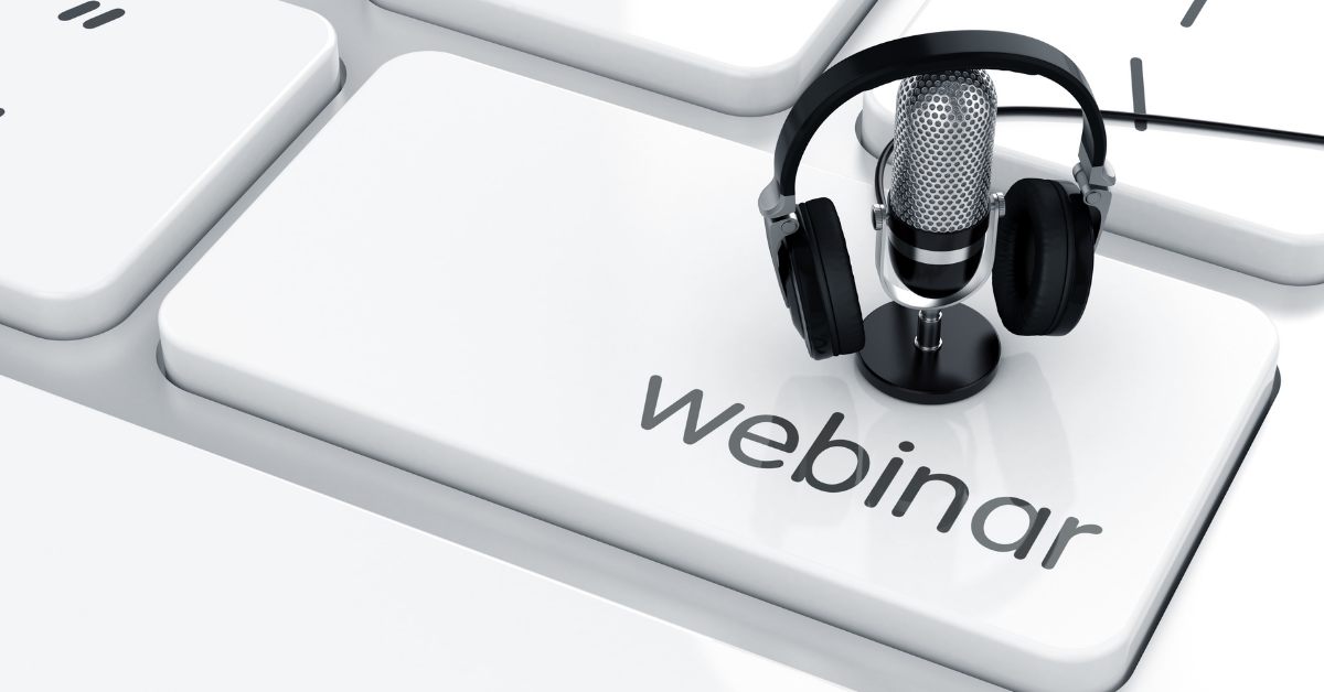 A webinar with numerous attendees blurred on a computer screen with a microphone in the forefront