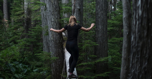 A woman balancing on a board in a forest